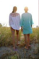 Two young women walking over dunes in the evening sun