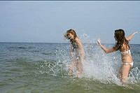Young woman splashing water onto her friend, blurred motion