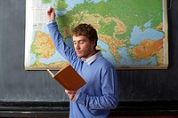 Young man with a book in his hand is standing in front of a map