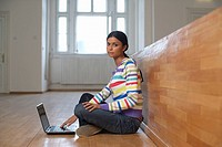 Young Indian woman in an auditory is sitting on the floor in front of a laptop