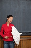 Asian woman is holding an umbrella in front of a blackboard