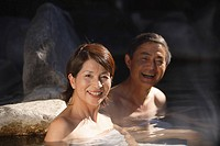 Middle_aged couple relaxing in natural hot spring