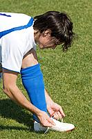 Soccer Player Tying His Boot