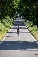 Cyclist riding bicycle on deserted road, front view (thumbnail)