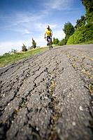 Cyclist riding bicycle on a cracked road, front view (thumbnail)