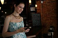 Young happy woman text messaging in cafe.