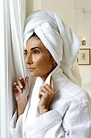 Woman in bathrobe and towel looking out bathroom window