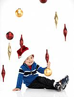 Boy 2_3 wearing santa hat, sitting under Christmas ornaments, studio portrait