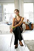 Young stylish woman sitting chair with men behind (thumbnail)