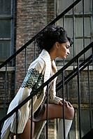 Young stylish woman walking up fire escape