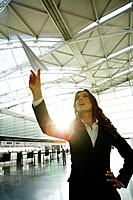Young businesswoman throwing paper airplane in airport