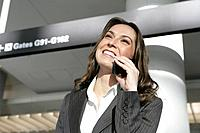 Young businesswoman on the phone in airport