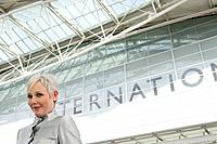 Mature woman standing in front of airport.