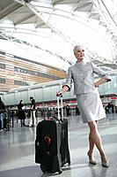 Mature woman standing in airport with luggage (thumbnail)