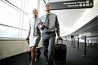 Mature couple walking to concourse in airport (thumbnail)