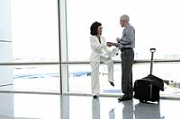Businesspeople shaking hands in airport.