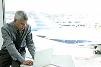 Mature businessman using laptop at airport.