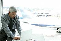 Mature businessman using laptop at airport.