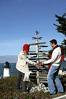 Young couple looking at direction post at lighthouse
