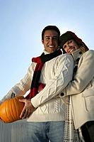 Portrait of young couple with pumpkin.