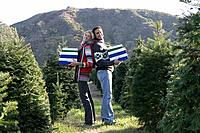 Young couple holding gift boxes in Christmas tree field.