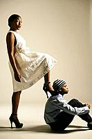 Young African American woman stepping on man, studio shot
