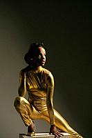 Young African American woman in gold bodysuit, studio shot