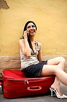 Indian woman traveling an talking with a red suitcase