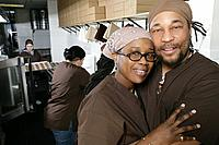 African American couple in restaurant kitchen.