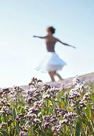 Young woman dancing in meadow, focus on foreground