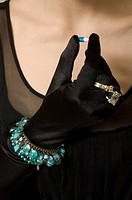 Young woman in elegant dress and gloves holding capsule, close up, mid section