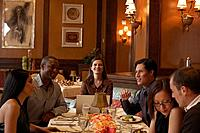 Group of people sitting at restaurant table, talking