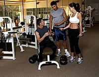 Two men and woman discussing in gym