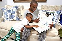 Father and son 6_7 looking at colouring book on sofa
