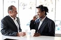 Two business men at bar counter holding coffee, smiling, one talking on mobile phone