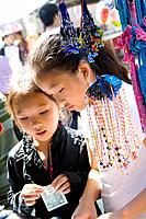 Hmong child holds money to buy jewelry at concession tent  Hmong Sports Festival McMurray Field St Paul Minnesota USA