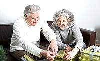 Senior couple sitting on sofa, wrapping presents