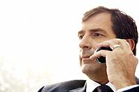 Mature businessman talking on cell phone, looking away