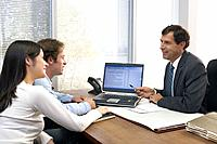 Man and woman meeting with businessman, businessman pointing at laptop