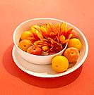 Peaches and exotic flower in modern fruit bowl