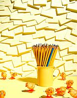 Wind_up chickens surrounding mug of pencils, with notepad background