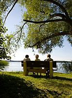 Three people sitting on park bench by lake, rear view