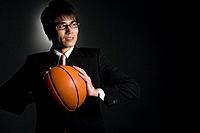 Businessman holding basketball, studio shot