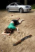 Murder scene. Dead woman lying on the ground near a shotgun.