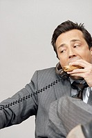 Business man using phone while eating sandwich, studio shot
