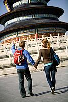 China, Beijing, couple walking by temple, rear view