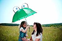 Woman and girl playing with umbrella