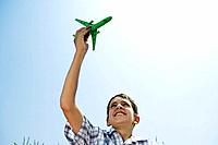 Boy holding toy plane aloft