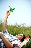 Boy lying down playing with plane