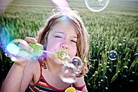 Girl blowing bubbles to camera